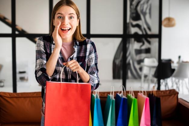 Mujer contando un secreto y sosteniendo una bolsa de papel Foto gratis