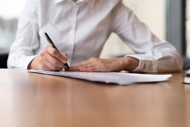 Mujer corporativa escribiendo en papel Foto gratis