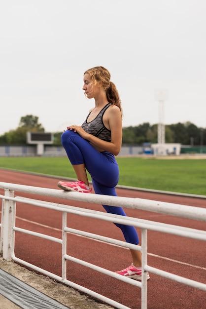 Mujer corredor estiramiento antes de maratón Foto gratis