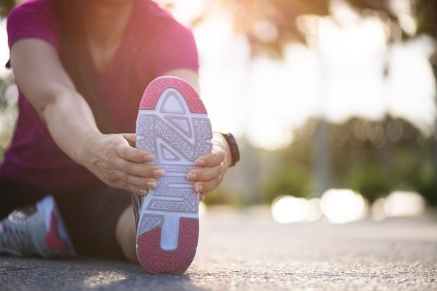 Mujer corredor sentarse en la carretera estirando las piernas antes de correr en el parque. Foto Premium