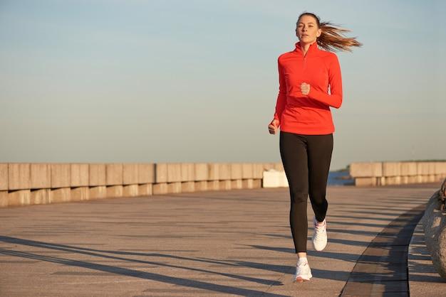 Una mujer corriendo en camisa roja y leggins negros en la calle al amanecer. corriendo en el muelle de hormigón Foto Premium
