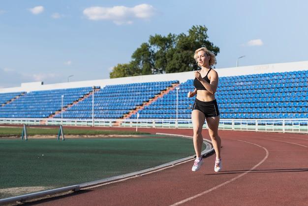 Mujer corriendo entrenamiento en el estadio Foto gratis