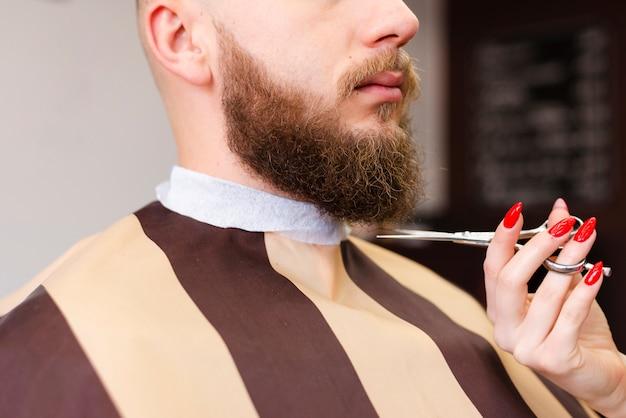 Mujer cortando la barba de un hombre en una peluquería profesional Foto gratis