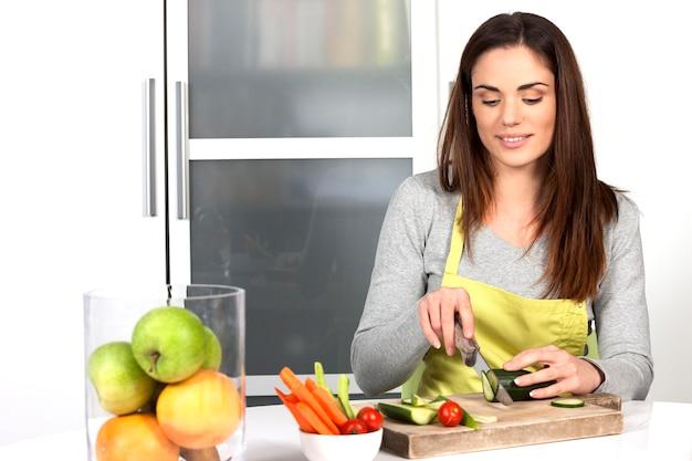 Mujer cortando pepino y verduras en la cocina Foto gratis