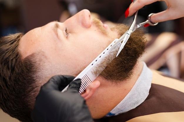 Mujer cortando el primer plano de barba de un cliente Foto gratis