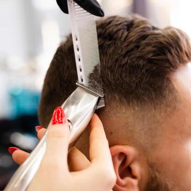 Mujer cortando el primer plano de cabello de su cliente Foto gratis
