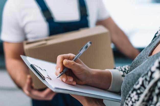 Mujer de la cosecha que firma para el paquete Foto gratis