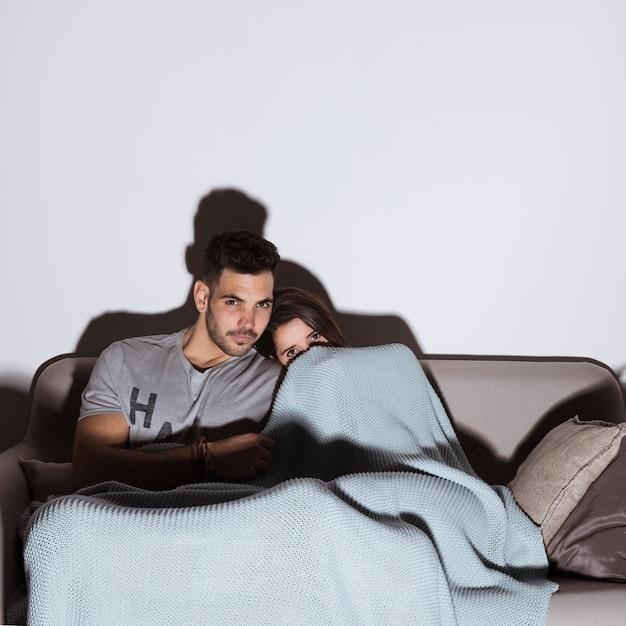Mujer en coverlet y hombre guapo viendo la televisión en el sofá en una habitación oscura Foto gratis