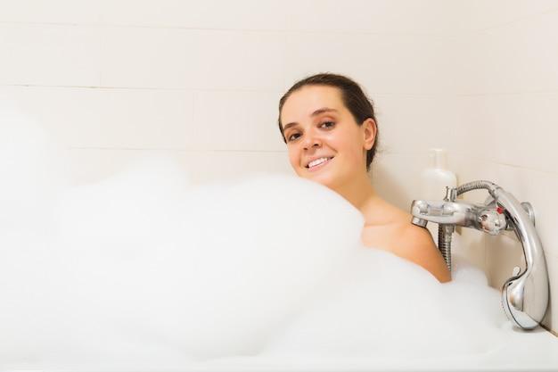 Mujer cubierta de espuma en el baño Foto gratis