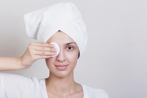 Mujer cubriendo un ojo con disco de maquillaje Foto gratis