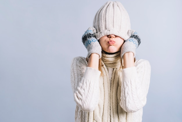 Mujer cubriéndose la cara con gorra y soplando las mejillas. Foto gratis