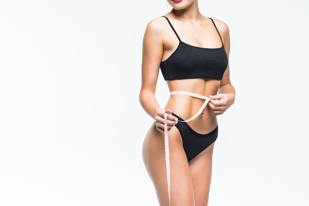 Mujer de cuerpo femenino con cinta de centímetro alrededor en la pared blanca. Foto gratis