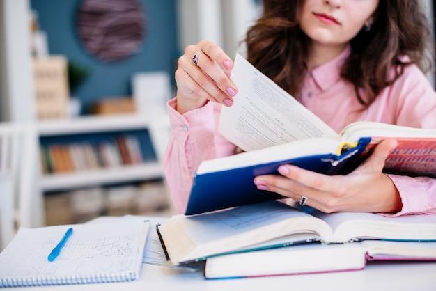 Mujer de cultivos leyendo libros de texto en la biblioteca Foto gratis