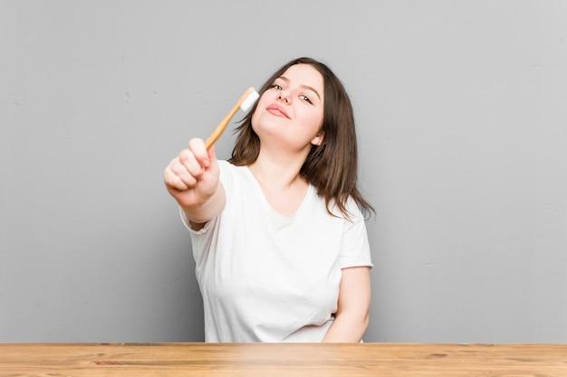 Mujer con curvas caucásica joven que limpia sus dientes con un cepillo de dientes aislado en una pared gris Foto Premium