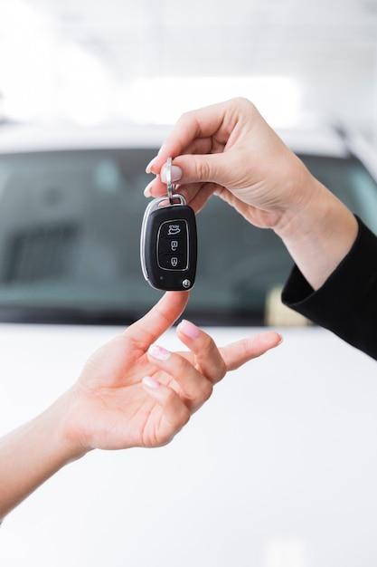 Mujer dando llaves a otra mujer Foto gratis