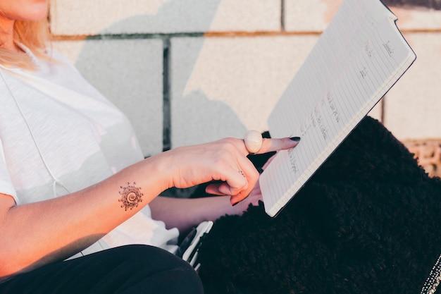 Mujer de la cosecha que señala en estudiar del libro Foto Gratis