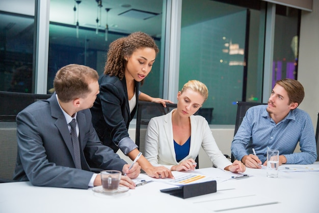 Mujer de negocios enseñando un documento a unos compañeros Foto Gratis