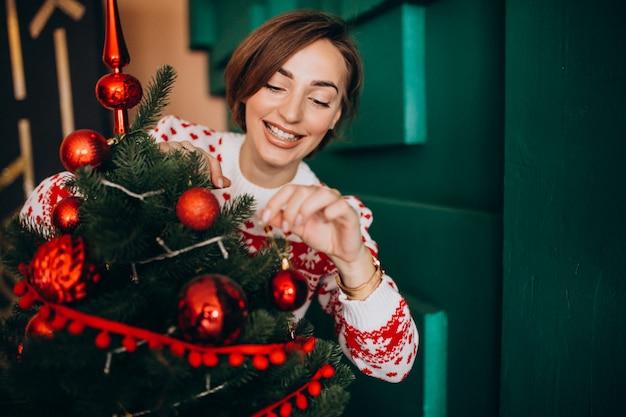 Mujer decorando el árbol de navidad con bolas rojas Foto gratis