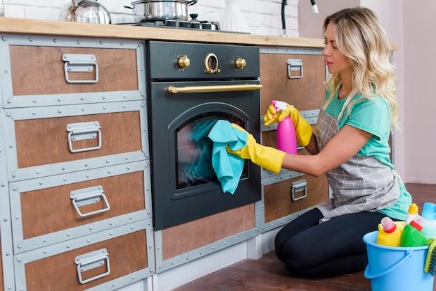 Mujer en un delantal en la cocina lavando la puerta del horno Foto gratis