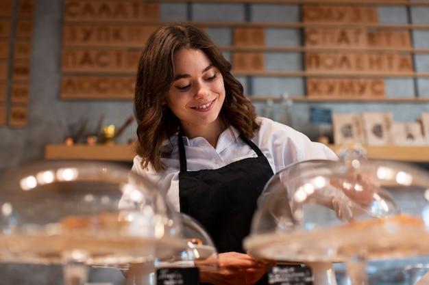 Mujer en delantal trabajando en cafetería Foto gratis