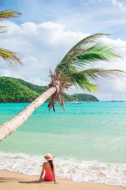 Mujer delgada joven en el sombrero del bikini y de paja que miente en la playa tropical. hermosa chica bajo la palmera en aguas poco profundas Foto Premium