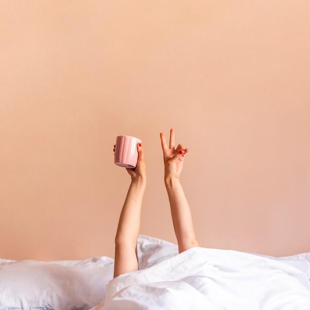 Mujer dentro de la cama con las manos arriba Foto gratis
