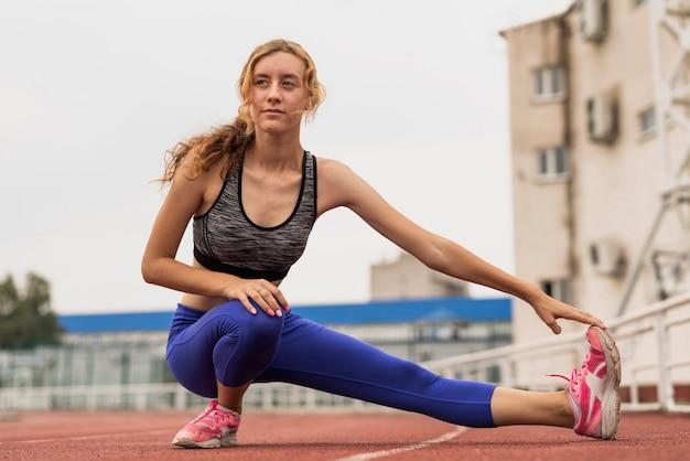 Mujer deportiva de ángulo bajo calentamiento Foto gratis