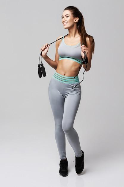 Mujer deportiva de la aptitud joven que presenta sonriendo llevando a cabo la cuerda de salto en blanco. Foto gratis
