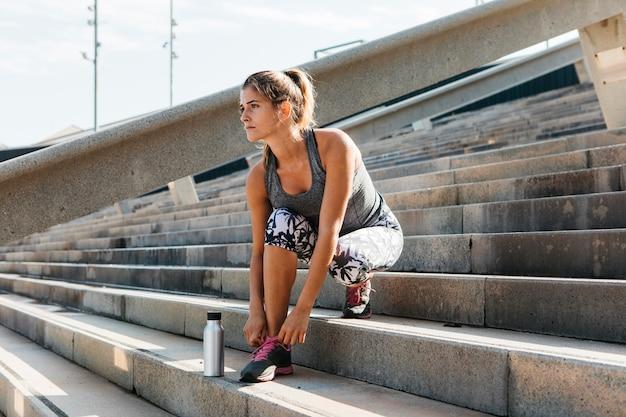 Mujer deportiva atando zapatos en entorno urbano