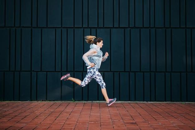 Mujer deportiva corriendo en entorno urbano Foto gratis