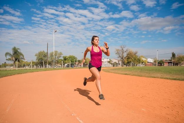 Mujer deportiva corriendo en pista de estadio Foto gratis