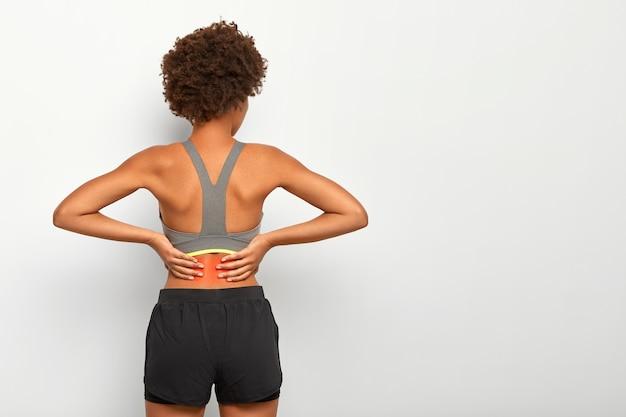 Mujer deportiva con corte de pelo afro toca la cintura con ambas manos, siente dolor en la columna vertebral, muestra la ubicación de la inflamación, usa top gris Foto gratis