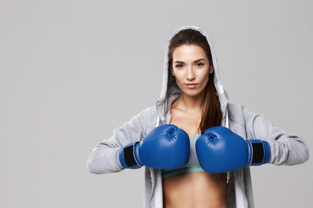 Mujer deportiva con guantes de box azul entrenamiento en blanco. Foto gratis