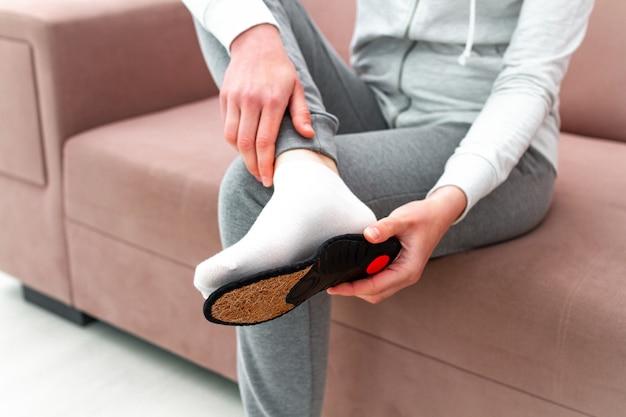Mujer deportiva que ajusta plantillas ortopédicas en casa. tratamiento y prevención de pies planos y enfermedades del pie. cuidado de los pies, comodidad de los pies. cuidado de la salud, usar zapatos cómodos Foto Premium
