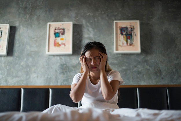 Mujer deprimida con dolor de cabeza mano sosteniendo su cabeza en la cama Foto gratis