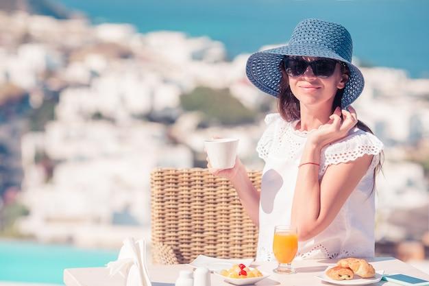 Mujer desayunando en un café al aire libre con una vista increíble de la ciudad de mykonos. Foto Premium