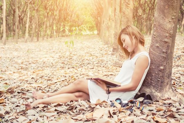 Mujer descalza disfrutando un libro Foto Gratis