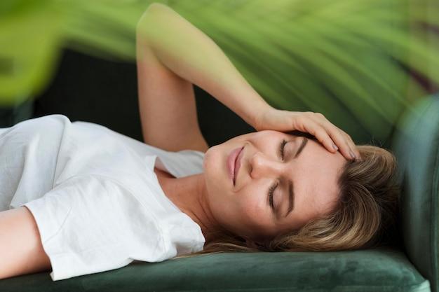 Mujer descansando en el sofá y planta borrosa Foto Premium