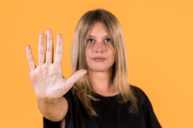 Mujer desenfocada mostrando parada gesto en lenguaje de señas Foto gratis