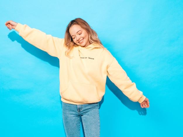Mujer despreocupada atractiva que presenta cerca de la pared azul. modelo positivo divirtiéndose. levantando sus manos Foto gratis