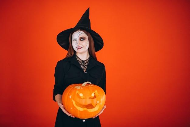 Mujer en un disfraz de halloween con una calabaza Foto gratis