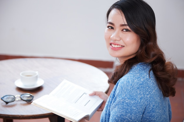 Mujer disfrutando de café y libro Foto gratis