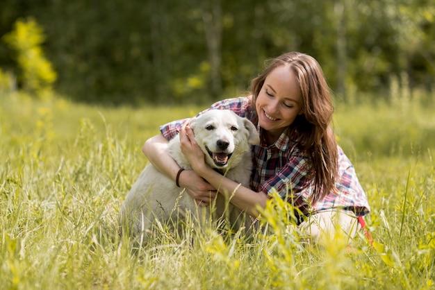 Mujer disfrutando con un perro en el campo Foto gratis