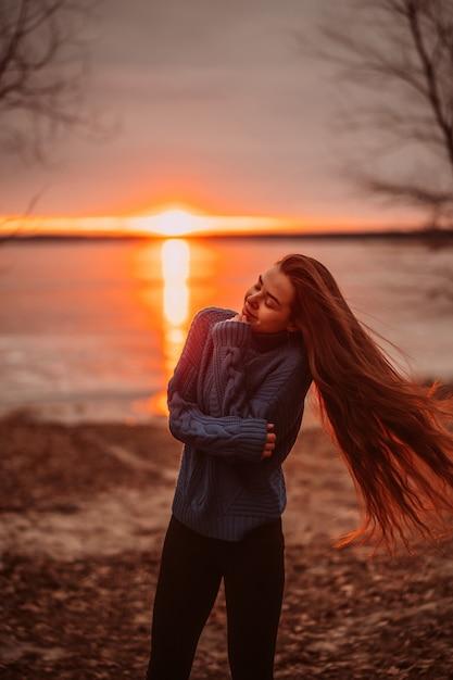 Mujer disfrutando de tiempo relajante junto al hermoso lago al amanecer Foto gratis