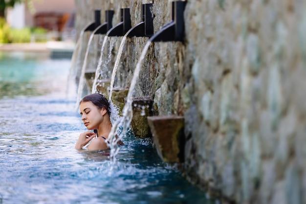Mujer disfrutando de vacaciones en el lujoso complejo hotelero frente al mar con piscina y paisaje tropical cerca de la playa Foto Premium