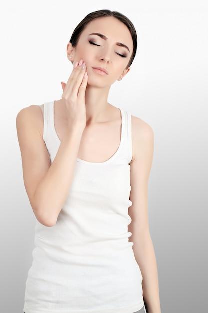 Mujer en dolor. primer plano de hermosa mujer joven sensación dolorosa dolor de muelas, tocando la cara con la mano. triste niña estresada sintiendo fuertes dientes, mandíbula o dolor de cuello. salud y cuidado dental. Foto Premium