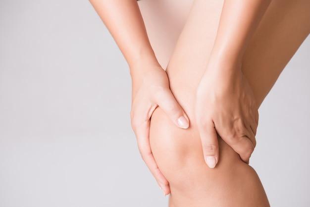 Mujer en el dolor de rodilla mientras se ejecuta. concepto de salud y médico. Foto Premium
