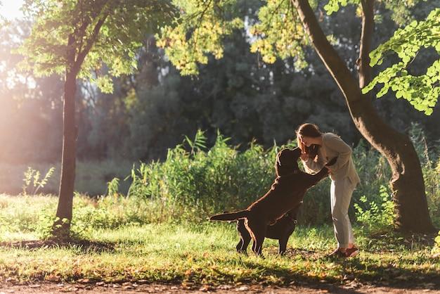 Mujer y dos perros jugando en el parque Foto gratis