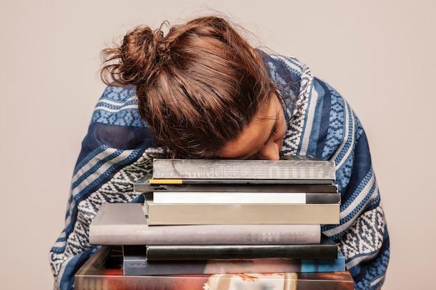 Mujer durmiendo en pila de libros