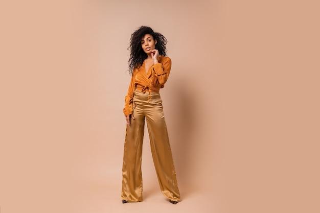 Mujer Elegante En Blusa Naranja Y Pantalones De Seda Dorados Posando Sobre Pared Beige Tacones Altos Increibles Pelos Ondulados De Longitud Completa Foto Gratis